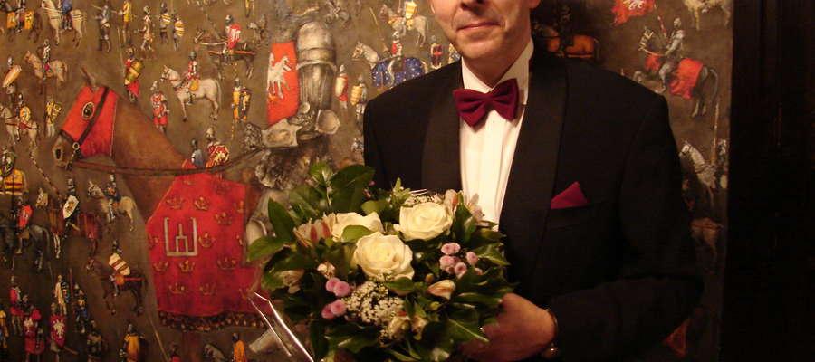 Wojciech Popielarz po koncercie w Brukseli na tle jednego z obrazów Grunwald Art 2010
