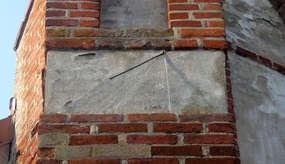 Jeden z zegarów słonecznych na murze kościoła w Wozławkach