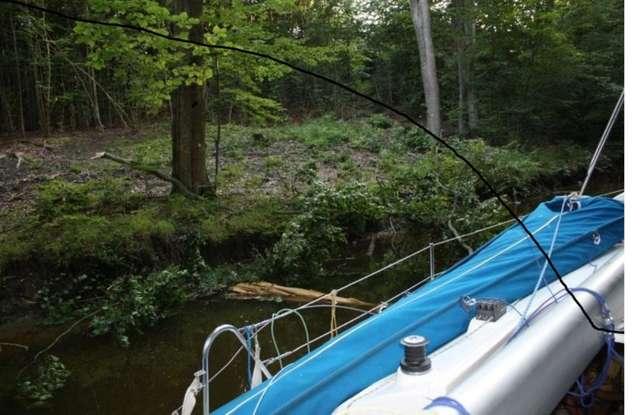 Jacht państwa Sędkiewiczów wpłynął na kłodę w wąskim kanale Duckim, łączącym jeziora Ruda Woda i Bartężek - full image