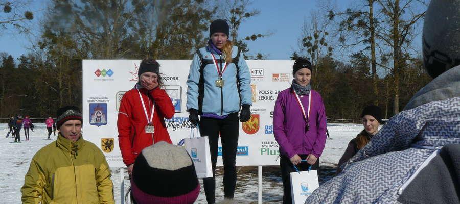 Klaudia Owczarek na najwyższym stopniu podium, tuż po tym, jak złoty medal zawiesił na jej szyi trener Mirosław Figat (z lewej)