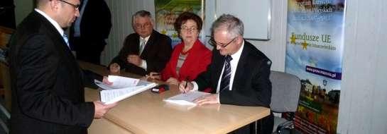 Burmistrz i skarbnik gminy w trakcie podpisania umowy o dofinansowanie