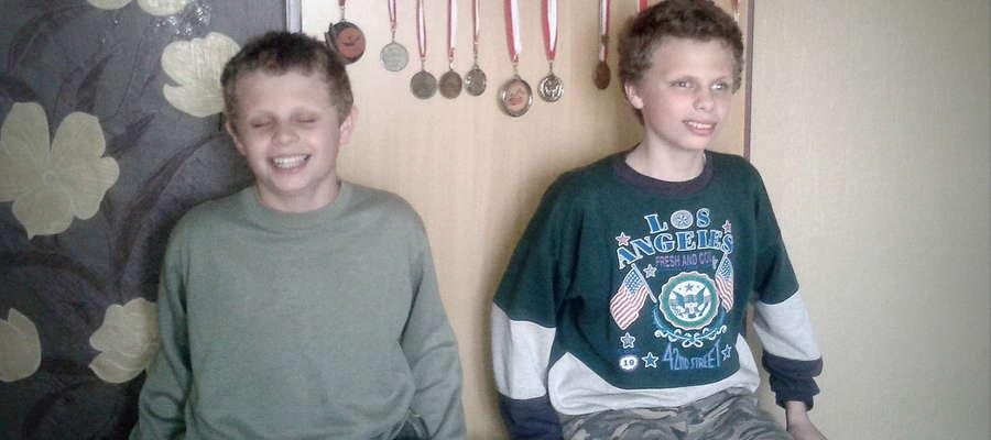 Bliźniacy ze Sławęcina. Na ścianie za nimi wiszą medale, które zdobyli na zawodach sportowych