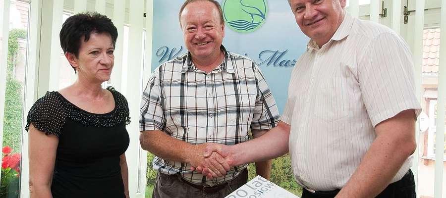 Adam Krzyśków (z prawej)– prezes WFOŚiGW w Olsztynie wręcza umowę dofinansowania Jarosławowi Kuczyńskiemu, wójtowi gminy Wieliczki. Na zdjęciu ze skarbnik gminy Wiesławą Dowejko.
