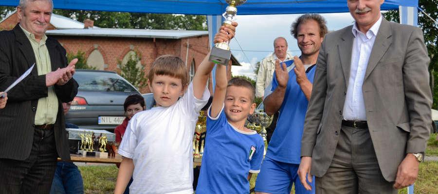 Najmłodsi piłkarze turnieju w 2012 roku, Kacper Szewera i i Oskar Szalkowski (trzymają puchar, Kacper jest z lewej strony) w otoczeniu organizatorów Dni Sportu. Pierwszy z prawej burmistrz miasta i gminy Kisielice Tomasz Koprowiak, obok Karol Banaś z Klim