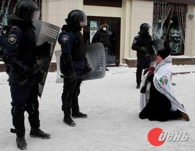 Kobieta klęcząca przed milicjantami: pobijcie mnie zamiast staruszka - full image