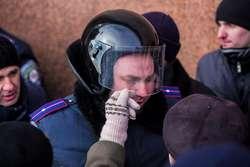 Płaczący policjant. Łzy wyciera mu demonstrantka