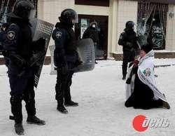 Kobieta klęcząca przed milicjantami: pobijcie mnie zamiast staruszka