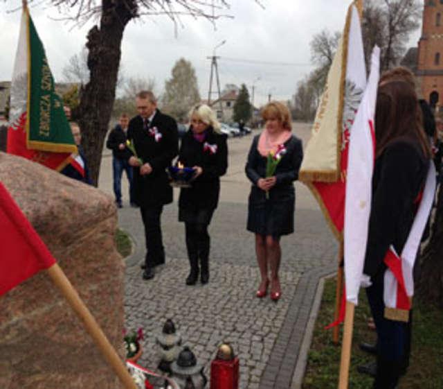 Pod pomnikiem złożono kwiaty i zapalono znicze - full image