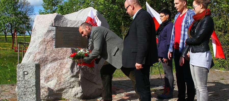 Na zdjęciu Tomasz Węgrzynowski składa kwiaty pod pomnikiem, obok stoi Robert Szaj