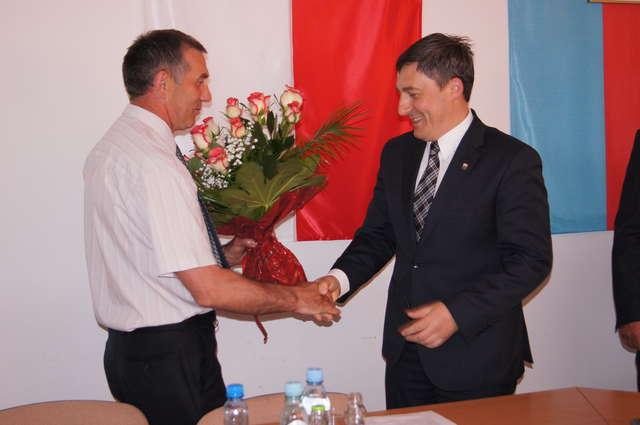Kwiaty na ręce wójta Rafała Kowalczyka składa przewodniczący rady gminy Wąsewo, Krzysztof Gałązka - full image