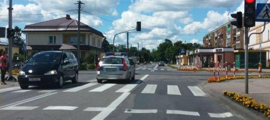 Na skrzyżowaniu pali się czerwone światło. Policyjny samochód mimo to przejeżdża przez nie