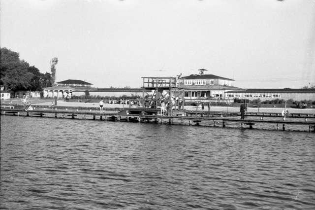 Plaża widziana od strony jeziora, zdjęcie wykonano prawdopodobnie z kajaka lub roweru wodnego. Na pierwszym planie skocznia i pomosty, dalej zabudowania z restauracją i przebieralniami - full image