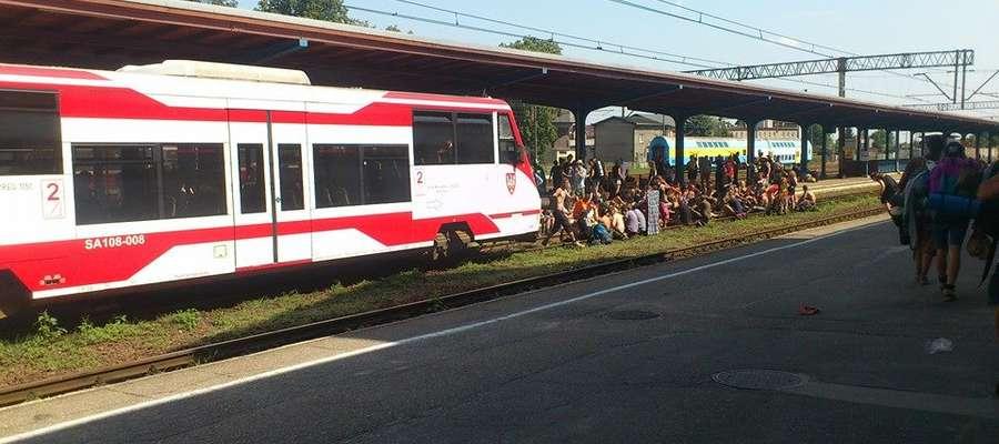 Niedoszli pasażerowie usiedli na torach, przed pociągiem, w którym zabrakło dla nich miejsca