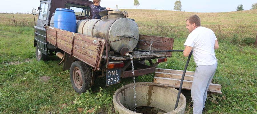 Tomasz Gricman przywozi wodę z centrum wsi i wlewa ją do studni. To woda do mycia i prania. Tę do pici kupują butelkowaną.