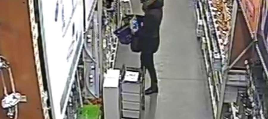 Kobieta chowa skradziony towar do torby