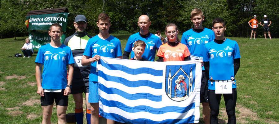 Biegacze z Budowlanki startujący w VIII Letnim Biegu Sasinów, tradycyjnie z flagą. Sportowcy z Iławy zawsze podkreślają, skąd pochodzą