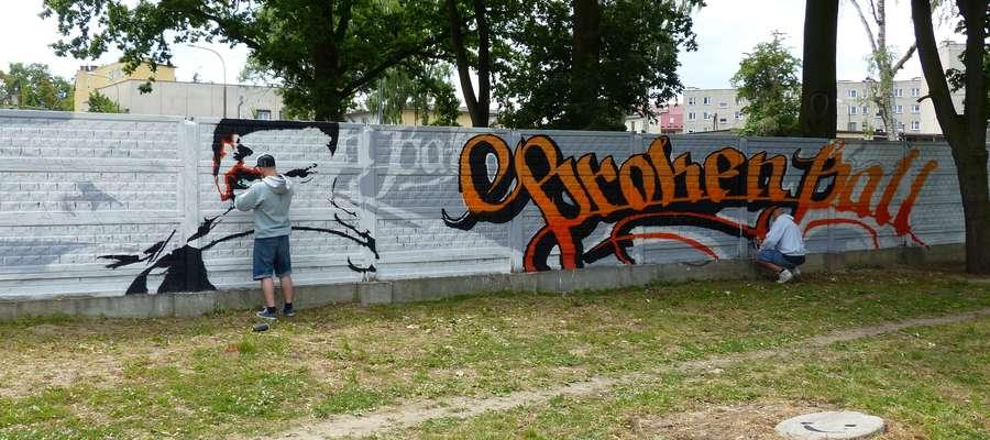 Dziś (piątek, 19. czerwca), godzina 12:30 — Mateusz Wilczek i Maciej Gryko podczas pracy nad graffiti. Powstaje ono na murze znajdującym się tuż przy ścieżce pieszo-rowerowej nad rzeką Iławka