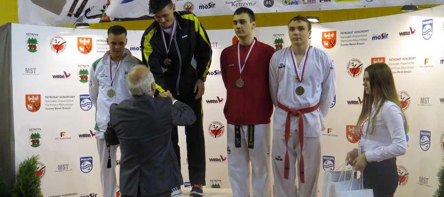 Artur Trumiński (Tygrys Kętrzyn, w ciemnym stroju) na najwyższym podium Młodzieżowych Mistrzostw Polski. Artur wygrał w kategorii do 87 kg.