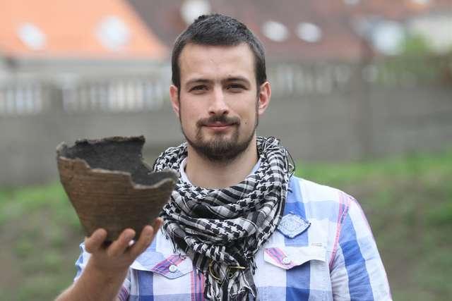 Kacper Martyka, archeolog z Muzeum Warmii i Mazur w Olsztynie z urną z grobu ciałopalnego - full image