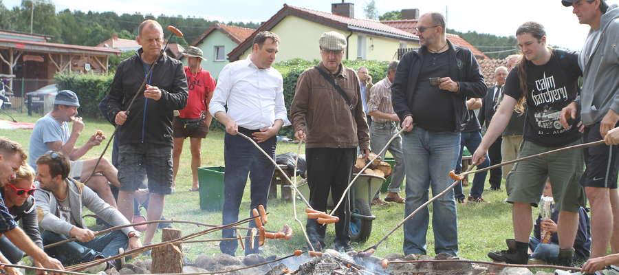 Po sprzątaniu wszyscy spotkali się przy ognisku na pieczeniu kiełbasek. Tomasz Makowski (w białej koszuli, obok Rafał Szczepański) podkreślał, że taka akcja to nie tylko pożytek dla środowiska, ale i integracja mieszkańców