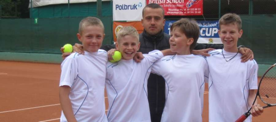 Uśmiechnięci młodzi tenisiści Budowlanych Olsztyn oraz ich trener Paweł Umbras