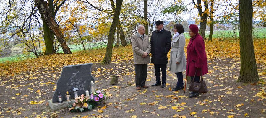 Delegacja na cmentarzyku w Łąkorku, którym opiekuje się wolontariusz z gminy Biskupiec