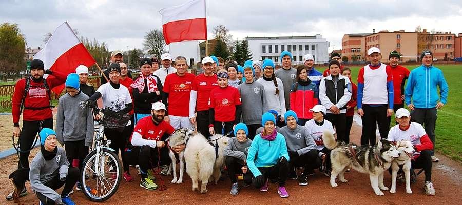 Silna ekipa biegaczy w towarzystwie rozbieganych czworonogów na płońskim stadionie tuż przed startem z okazji Święta Niepodległości