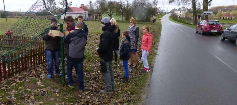 Dzieci pomagały pracownikom firmy Janpol w mocowaniu tabliczek do koszy