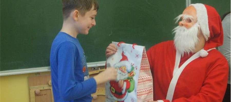 Uczeń szkoły w Gwiździnach odbiera paczkę od Mikołaja