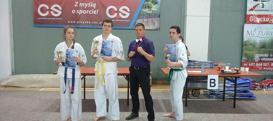 Trójka medalistów ze swoim trenerem.