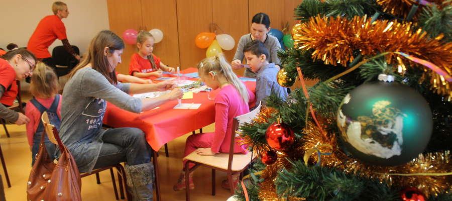 Dzieci z rodzicami tworzą seniorom świąteczne obrazki