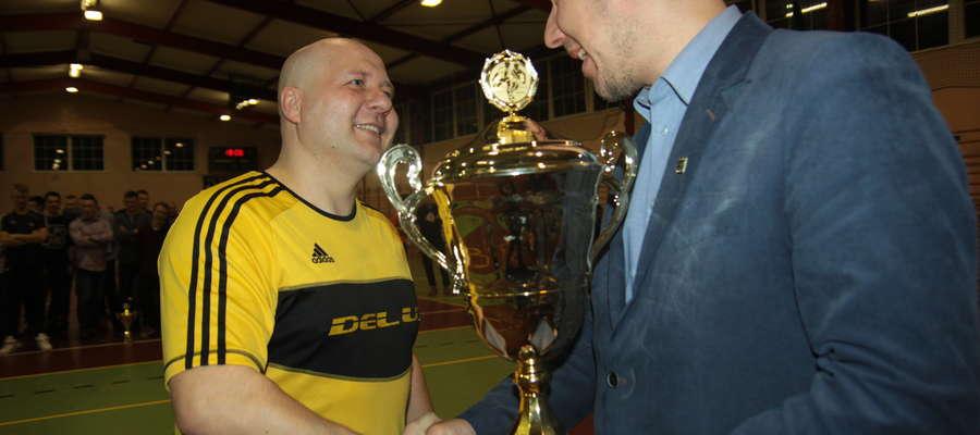 Tomasz Deluga (z lewej) odbiera puchar za zwycięstwo Deluxu w 16. mistrzostwach powiatu w futsalu