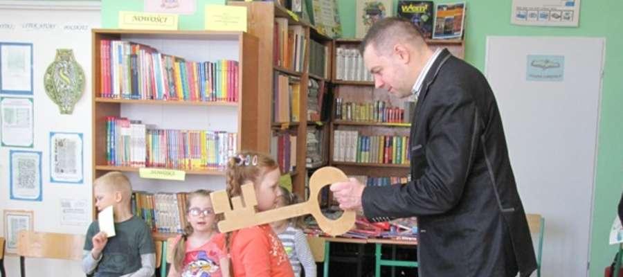 Bibliotekarz – dotykając ramienia każdego z uczniów drewnianym kluczem – uroczyście pasował nowych Czytelników szkolnej biblioteki