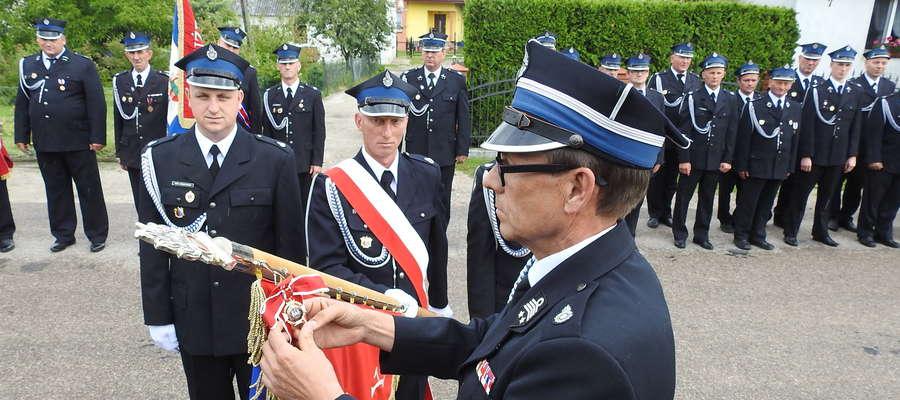 Starosta Andrzej Ochlak, członek zarządu OW ZOSP dekoruje sztandar OSP w Zwiniarzu Złotym Znakiem Związku