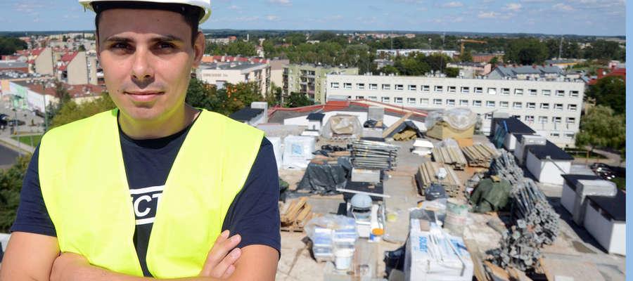 Inżynier Marcin Toczek osobiście nadzoruje wszystkie prace. W tle plac budowy, czyli dach szpitala