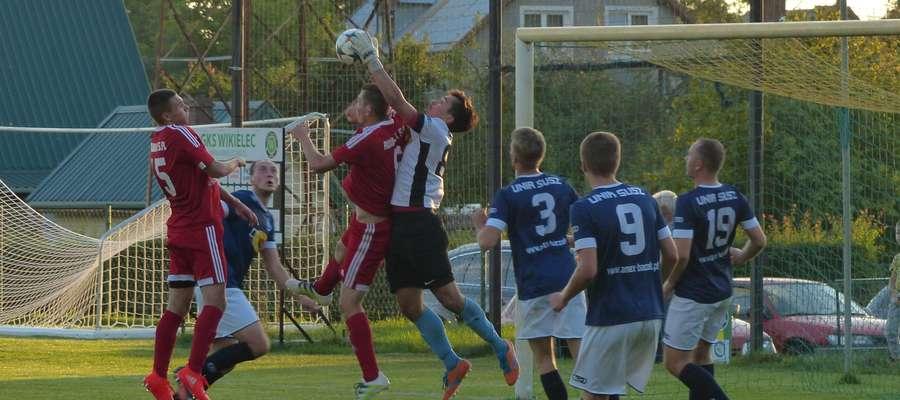 Kamil Jędrzejewski (bramkarz Amex Bączek Unii Susz) walczy o piłkę z piłkarzami GKS-u Wikielec