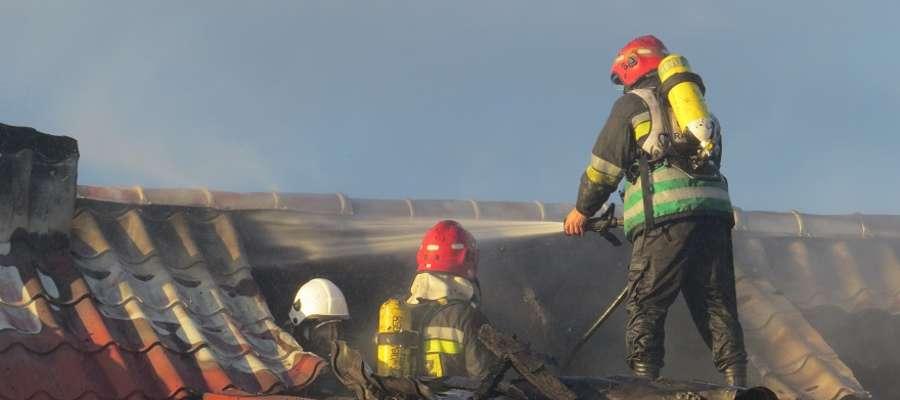Na poddaszu spalonego budynku strażacy gasili tlące się jeszcze elementy dachu.