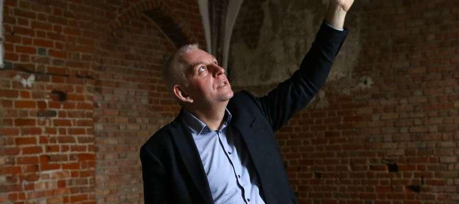 Burmistrz miasta Grzegorz Mrowiński objaśnia zakres robót restauracyjnych w kaplicy pokrzyżackiego zamku gotyckiego w Działdowie