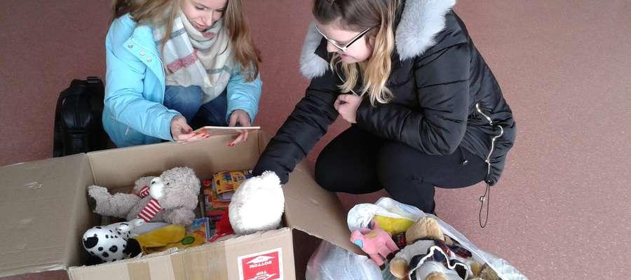 Oliwia i Klaudia przeglądają zebrane zabawki