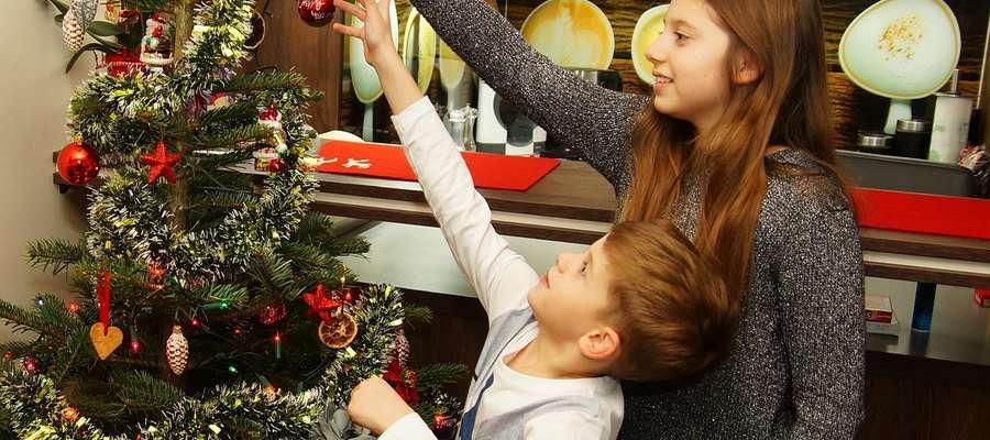 Na zdjęciu dzieci Ani oraz Sebastiana Furtaków przygotowują świąteczną choinkę w nowym domu
