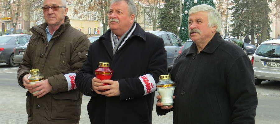 Andrzej Michalski (w środku) w towarzystwie Ryszarda Olechnowicza i Andrzeja Balika składa kwiaty pod tablicą pamiątkową na ratuszu miejskim.