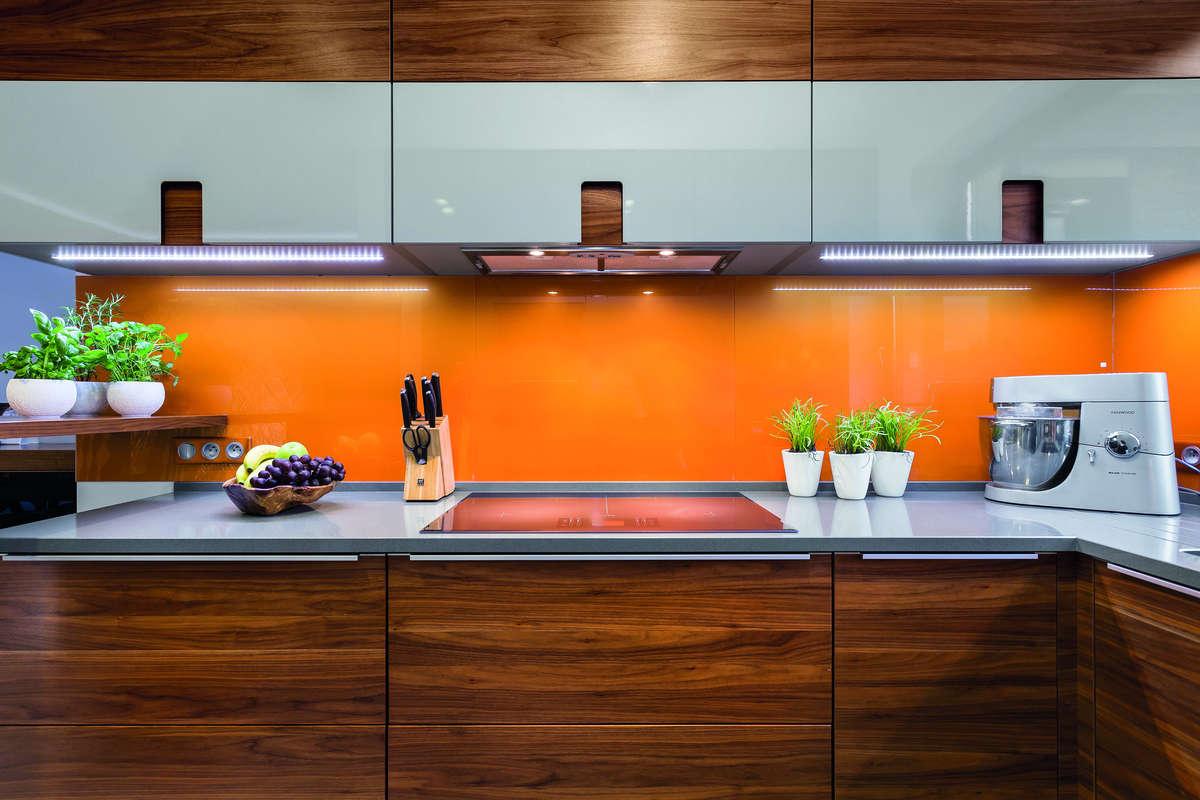 Pomarańczowe szkło nad blatem kuchennych świetnie wpisuje się w nowoczesną kuchnię. - full image