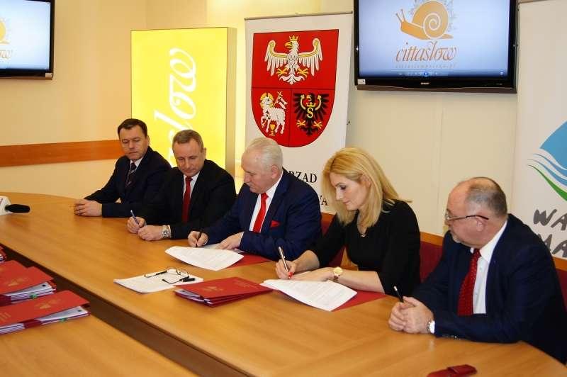 Marszałek województwa warmińsko-mazurskiego Gustaw Marek Brzezin (w środku) podpisuje kolejną pre-umowę - full image
