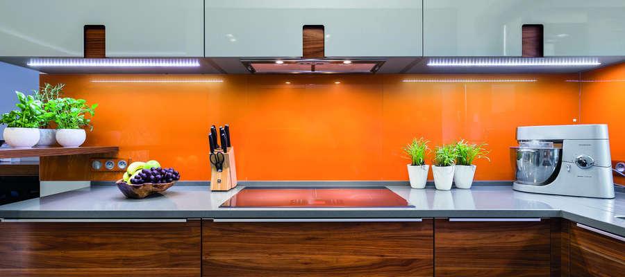 Pomarańczowe szkło nad blatem kuchennych świetnie wpisuje się w nowoczesną kuchnię.