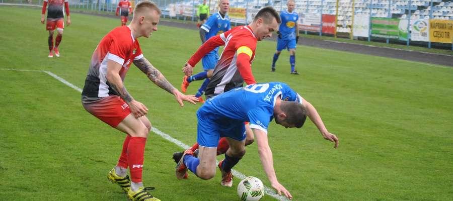 Obrońcy Motoru Lubawa próbują odebrać piłkę Wojciechowi Figurskiemu, grającemu trenerowi Jezioraka