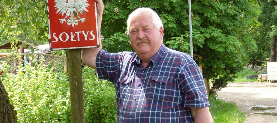 Leonard Jędrzejewski przed przedwojenną tabliczką sołtysa, którą umieścił przed swoim domem