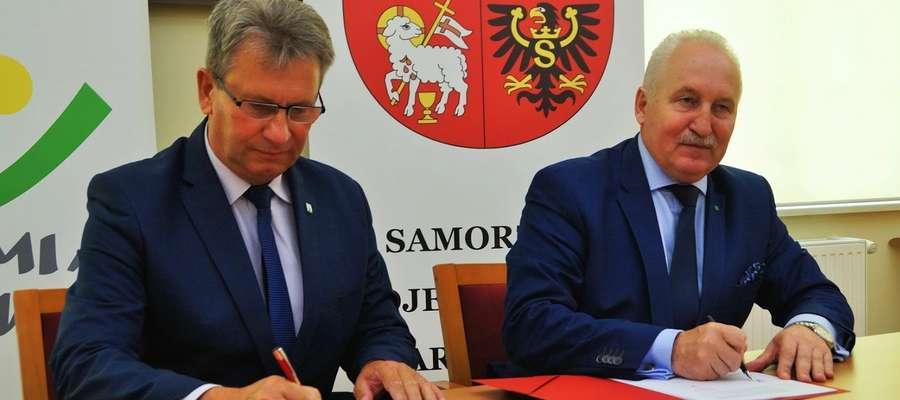 Burmistrz Susza Krzysztof Pietrzykowski (z lewej) i marszałek województwa Gustaw Marek Brzezin podpisują stosowne umowy