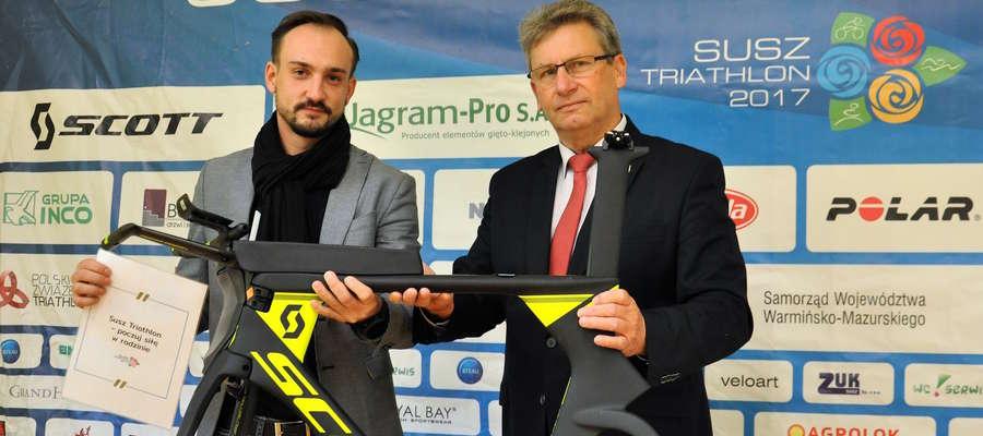 Burmistrz Susza Krzysztof Pietrzykowski (z prawej) wręcza nagrodę Pawłowi Dmowskiemu, który wygrałkonkurs na najciekawszy slogan promocyjny triathlonu