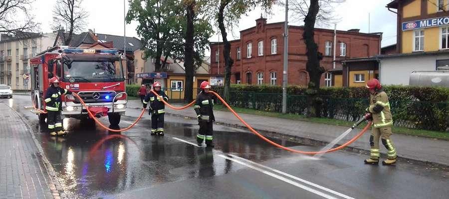Strażacy-ochotnicy usuwaja plamę ropopochodną z jezdni w centrum Susza