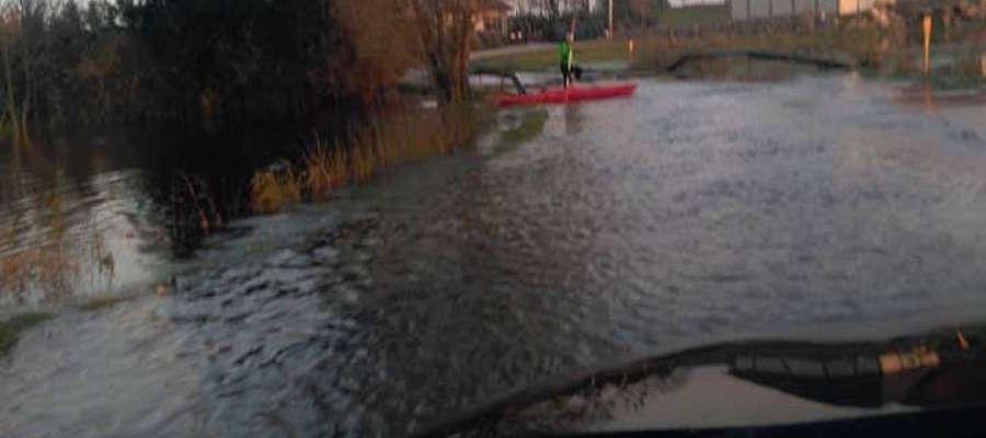 Próba przejazdu autem przez zalaną drogę. W tle widać, że mieszkańcy radzą sobie na różne sposoby, m.in. kajakiem pokonując odcinek